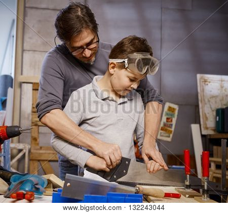 Father teaching son to use saw in workshop.