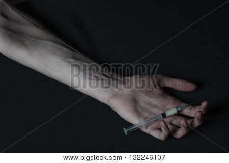 Addiction Theme: Hand Addict With Syringe With Drugs On A Dark Background