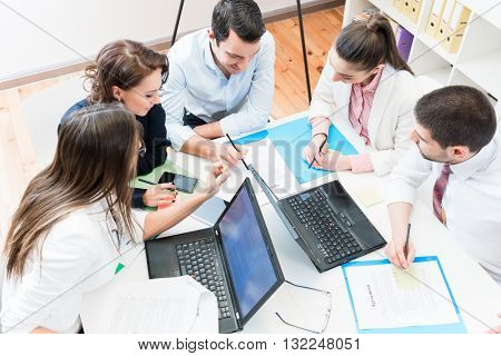 Business women and men in office negotiating contract or agreement in group meeting