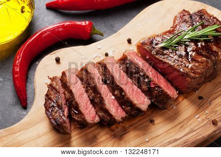 Grilled striploin sliced steak on cutting board over stone table