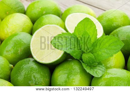 Fresh ripe limes with mint on wooden table