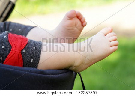 6 months old baby feet funny kicking on open air with bow tie on leggings