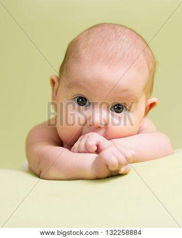 Baby teething. Infant kid sucks fingers lying on belly in nursery room