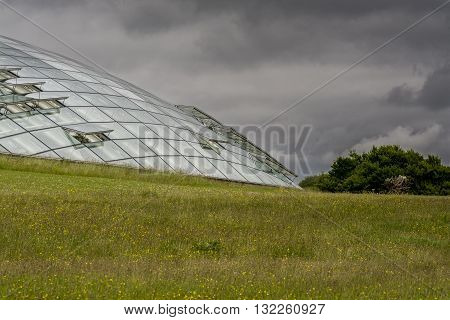 Futuristic eco dome made of glass panels set into a grass hillside, with a cloudy sky