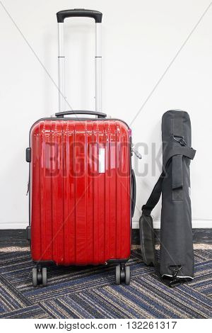 Red travelling suitcase and camera tripod stock photo