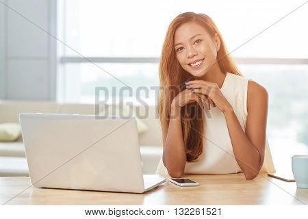Portrait of Filipino young woman sitting at her workplace