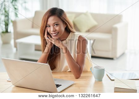 Pretty Filipino young woman working on laptop at home