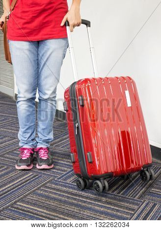 Passenger hand on red travelling suitcase stock photo