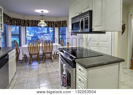 White outdated kitchen and dining area with island