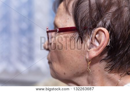 Profile of a senior woman with hearing aid.