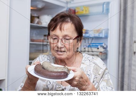 Happy senior woman holding a plate with pork liver sausages while standing in front of the open fridge in the kitchen.