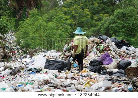 Penh Thailand - May 31 2016: Poor people searching on disposal site for useful things to recycle or resell in Northeast of Thailand.