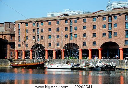 LIVERPOOL, UK - JUNE 11, 2015 - Yachts moored in Albert Dock with a pavement cafe to the rear Liverpool Merseyside England UK Western Europe, June 11, 2015.