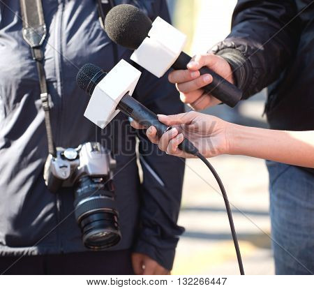 Journalists holding a microphones conducting an TV or radio interview