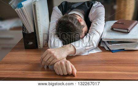 Tired Workaholic Is Sleeping On Desk In Office.