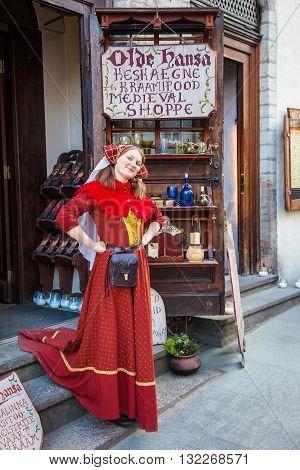 Tallinn Estonia - May 29 2016: Beautiful girl in red national medieval dress near medieval shop Olde Hansa in the Historical Centre of Tallinn city. Tallinn Estonia.
