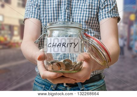 Man Standing On Street Is Collecting Money For Charity And Holds
