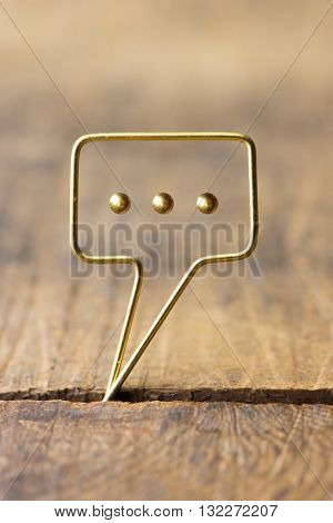 Golden tweet or remark. Blank speech bubble made of gold wire on rustic or grunge wood . Shallow depth of field.