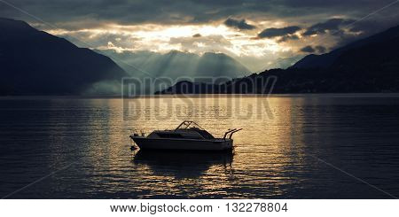Boat on Lake Como at the sunset. Silver linings in Lake Como at the sunset. Retro style photo. Sunset view of the lake in Lombardy. Varenna, Lake Como, Italy.