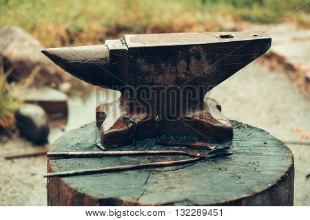 Old anvil and tongs on wooden stump on blurred background