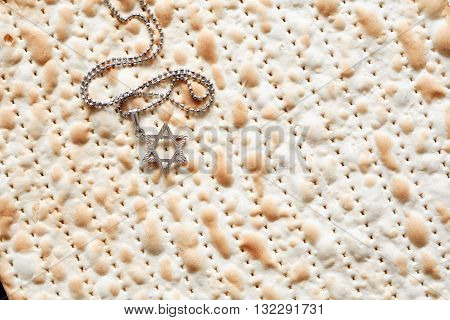 Seder concept. Star of David symbol lying on matzah background