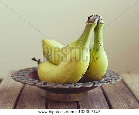Bananas in vintage bowl on wooden table