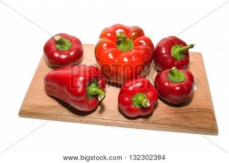 Several ripe peppers on a wooden cutting board.