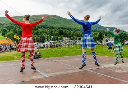 LOCHEARNHEAD SCOTLAND- JULY 242010: Three girls in traditional dress compete in a dance event at Highland Games in Lochearnhead.