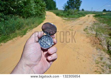 At the crossroads. Compass in the hand against the fork of the trail in the woods.