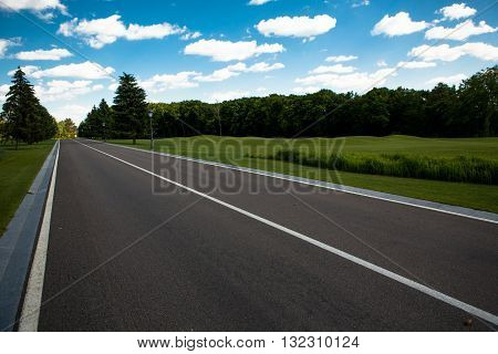 Bautiful road disappearing into horizon in middle of beautiful landscape with blue clouds. Beautiful road in deep green and yellow forest in wild.