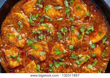 Chicken tikka masala close up texture, traditional spicy meat food with parsley
