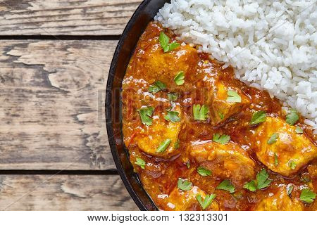 Chicken tikka masala traditional Asian spicy national meat food with rice and parsley in cast iron skillet on vintage wooden background. Karahi chicken or korma vindaloo recipe.