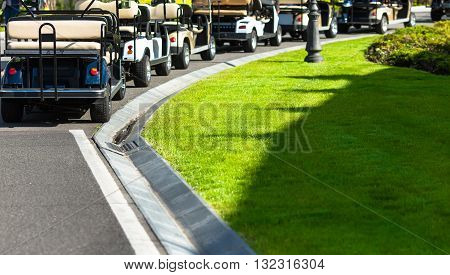 Golf carts not far from golf course. White golf carts at green golf course. Golf landscape in spring day.