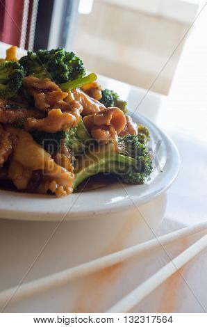 Chinese food chicken and broccoli take out with chopsticks