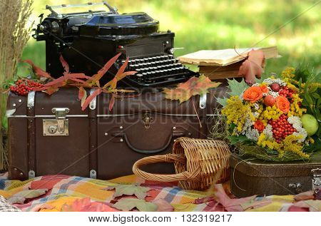Romantic autumn still life with books, plaid, vintage suitcase, old typewriter  and leaves