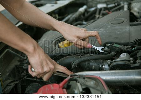 female hand with a wrench under the hood of the car.Woman car mechanic repairs automobile.