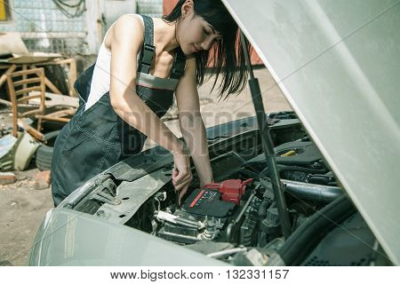 Attractive brunette Woman car mechanician repairs engine of car and smiles in the street near garage and trash