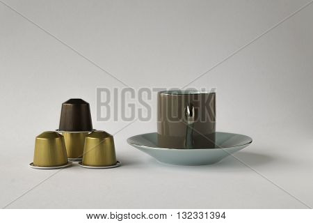 Espresso cup and saucer with coffee pods on white background