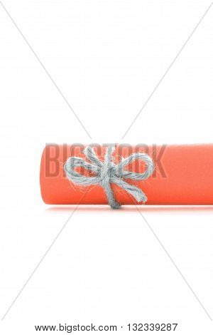Handmade natural cord knot tied on orange letter scroll isolated