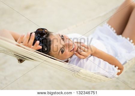 Tranquil happy woman relaxing lying on a hammock at the beach. Summer vacation relax and tranquility concept. Relaxed female resting outdoor.