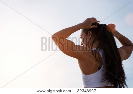 Epic back view of strong fit female athlete getting ready for workout towards the sun. Strong fitness woman tying ponytail. Motivation and healthy lifestyle concept.