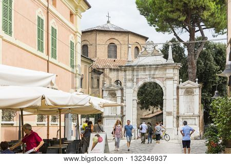 RAVENNA,ITALY-AUGUST 21,2015:people stroll in front the entrance of the San Vitale basilica in Ravenna-Italy during a cloudy day .