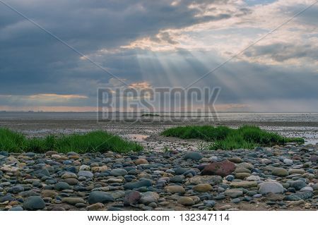 Rays of sunshine over a stony foreshore