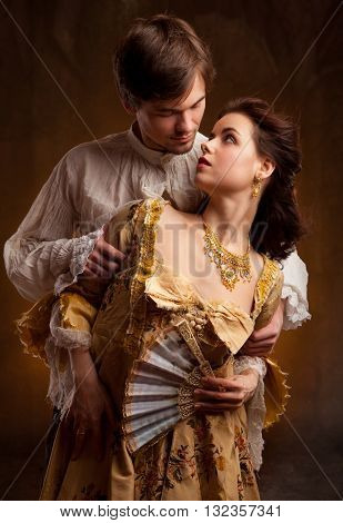pretty young lady in old time and man in medieval dress over red background
