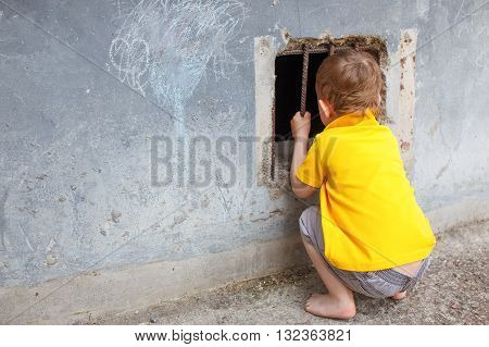 curious child looks into the barred window. a lost child in the street. copy space for your text