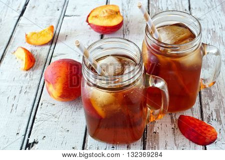 Two Mason Jar Glasses Of Homemade Peach Iced Tea On A Rustic White Wood Background