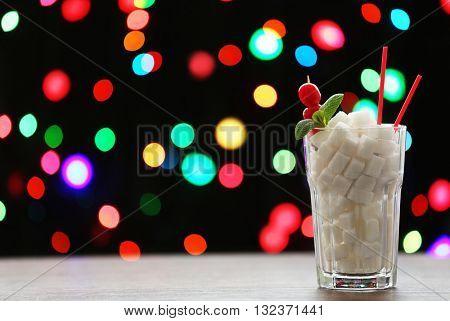 Highball glass with lump sugar on dark bokeh background