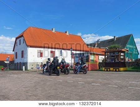 Old House And Bikers At The Embankment Of Venta River