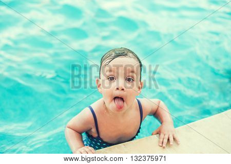 Happy child in swimming pool beautiful girl swims and showing tongue