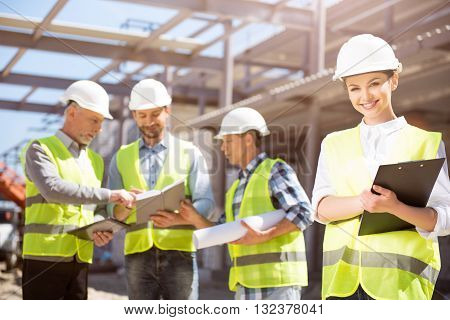 Construction site. A smiling and positive female engineer standing with papers with a group of engineers in a background